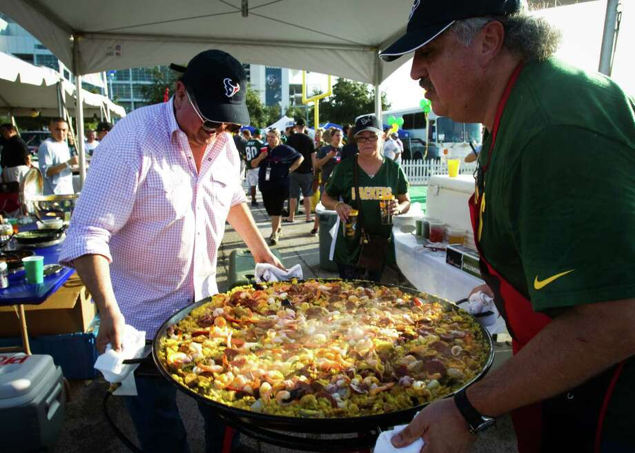 Alex Richards, left, and his brother Arnaldo Richards make paella during a tailgate party outside Reliant Stadium before the Houston Texans and Green Bay Packers Sunday Night Football game. Photo: Brett Coomer, Houston Chronicle / © 2012  Houston Chronicle
