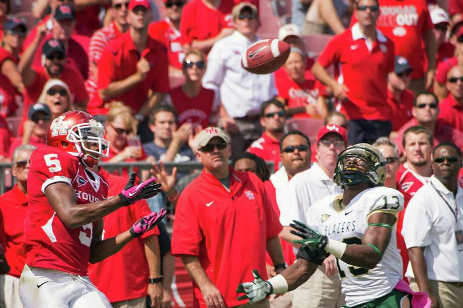 Houston running back Charles Sims (5) catches a pass as UAB cornerback Darius Powell (13) defends during the first half of a college football game at Robertson Stadium, Saturday, Oct. 13, 2012, in Houston. Photo: Smiley N. Pool, Houston Chronicle / © 2012  Houston Chronicle