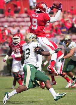 Houston wide receiver Dewayne Peace (9) makes a catch over UAB cornerback Darius Powell (13) during the first half of a college football game at Robertson Stadium, Saturday, Oct. 13, 2012, in Houston. Photo: Smiley N. Pool, Houston Chronicle / © 2012  Houston Chronicle