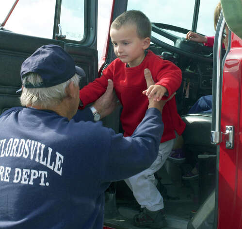 Noah Milot, 3, of New Milford enjoys his exciting experience aboard a firetruck by getting a lift to the ground from Gaylordsville volunteer firefighter Dave Williams during New Milford fire prevention day. Sept. 30, 2012. Photo: Trish Haldin