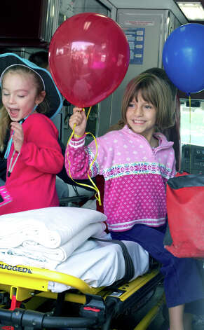 Five-year-olds Samantha Tripler, left, and  Hannah  Milot of New Milford make themselves right at home after climbing aboard a New Milford Community Ambulance vehicle during New Milford fire prevention day. Sept. 30, 2012 Photo: Trish Haldin