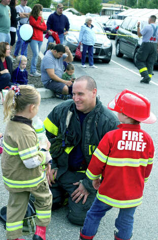Firefighter Al Thierfelder chats with his daughter, Calley Thierfelder, 4, and Jacob Weiss, 5, during New Milford fire prevention day. Sept. 30, 2012 Photo: Trish Haldin