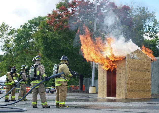 Gaylordsville volunteer firefighters battle a mock fire on a shed created and donated for New Milford fire prevention day by Home Depot. Sept. 30, 2012 Photo: Trish Haldin