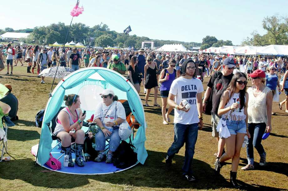 Music fans Keri Pearlsom, right and daughter Hana Pearlsom sit in their shade tent at the Austin City Limits Music Festival, Sunday, Oct. 14, 2012, in Austin, Texas. (Photo by Jack Plunkett/Invision/AP) Photo: Jack Plunkett, Associated Press / Invision