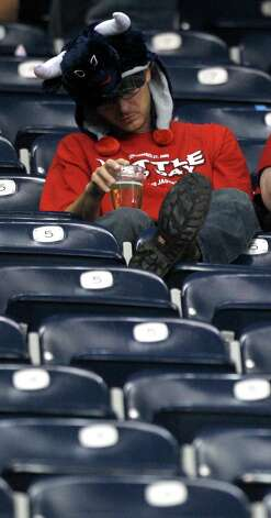 A Houston Texans fans sits in the stands with his head down during the fourth quarter against the Green Bay Packers at Reliant Stadium on Sunday, Oct. 14, 2012, in Houston. The Packers beat the Texans 42-24. ( Brett Coomer / Houston Chronicle ) Photo: Brett Coomer, Staff / © 2012  Houston Chronicle