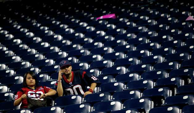 A pair of Houston Texans fans sit in the empty stands after the Texans lost to the Green Bay Packers at Reliant Stadium on Sunday, Oct. 14, 2012, in Houston. The Packers beat the Texans 42-24. ( Brett Coomer / Houston Chronicle ) Photo: Brett Coomer, Staff / © 2012  Houston Chronicle