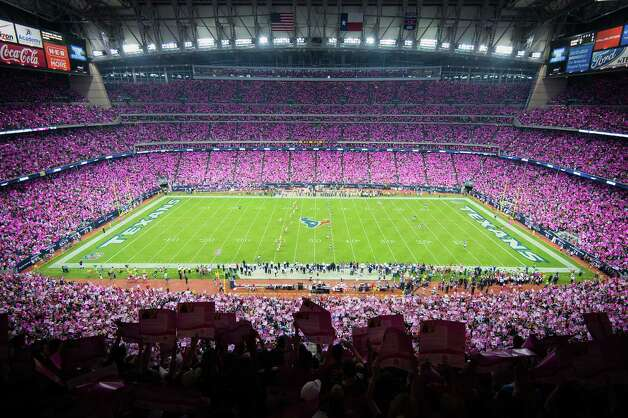 Fans paint the stadium pink with poster cards in recognition of Breast Cancer Awareness during the opening kickoff of the Green Bay Packers game against the Houston Texans at Reliant Stadium on Sunday, Oct. 14, 2012, in Houston. ( Smiley N. Pool / Houston Chronicle ) Photo: Smiley N. Pool, Staff / © 2012  Houston Chronicle