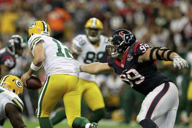 Green Bay Packers quarterback Aaron Rodgers (12) slips away from Houston Texans defensive end J.J. Watt (99) during the third quarter at Reliant Stadium, Sunday, Oct. 14, 2012, in Houston.  ( Nick de la Torre / Houston Chronicle ) Photo: Nick De La Torre, Staff / © 2012  Houston Chronicle