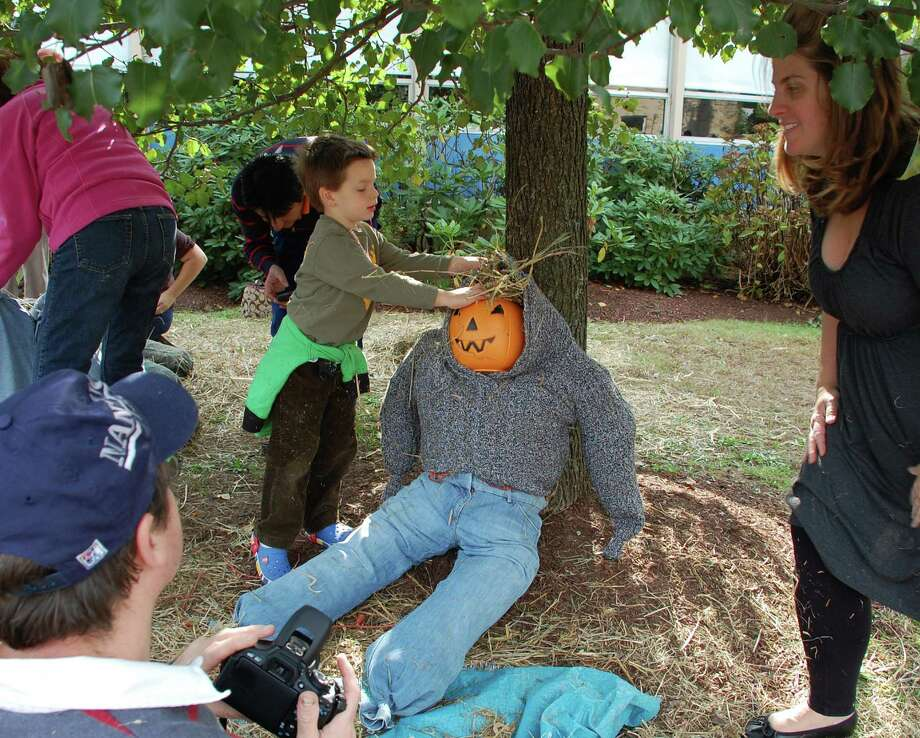 The Monahan family -- dad Brian, mom Kim, son Padraig, and daughter Finnigan -- assemble a scarecrow Sunday at the Assumption Scarecrow Festival. Photo: Jarret Liotta / Fairfield Citizen contributed