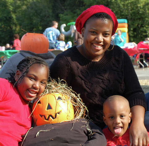 Nathalie Monfiston and her children Na'Cooksa, 8, and Lem, 3, pose with their scarecrow creation at Sunday's fundraiser for Assumption School. Photo: Jarret Liotta / Fairfield Citizen contributed