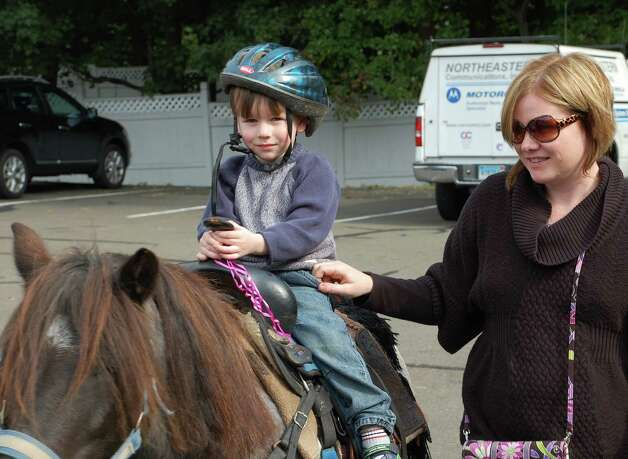 "Riley Lambert, 3, rides a pony named Tonka, accompanied by his mom, Monica, at Sunday's Scarecrow Festival at Assumption School. ""I wasn't scared,"" Riley said. ""I liked his wagging tail."" Photo: Jarret Liotta / Fairfield Citizen contributed"