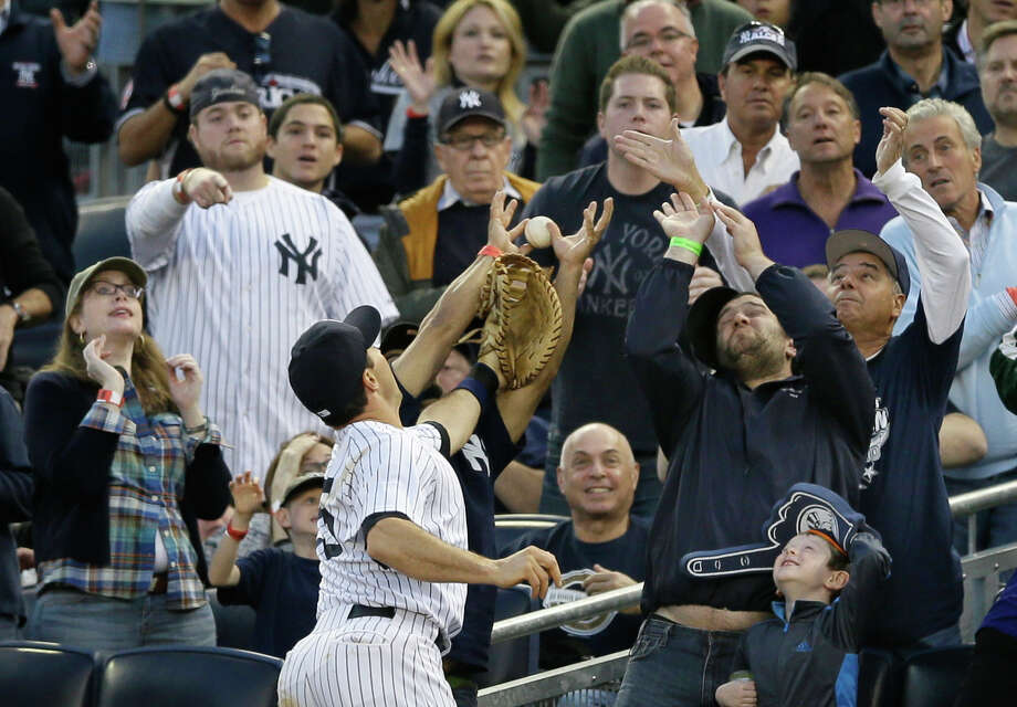 New York Yankees' Mark Teixeira reaches for a foul ball hit by Detroit Tigers's Delmon Young in the seventh inning of Game 2 of the American League championship series Sunday, Oct. 14, 2012, in New York. Photo: Matt Slocum, AP / AP