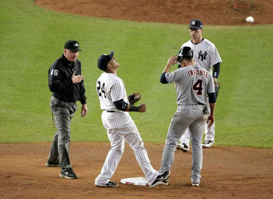New York Yankees' Robinson Cano, second from left, reacts after umpire Jeff Nelson called Detroit Tigers' Omar Infante safe at second base in the eighth inning of Game 2 of the American League championship series Sunday, Oct. 14, 2012, in New York. New York Yankees' Jayson Nix is at right. Photo: Charlie Riedel, AP / AP
