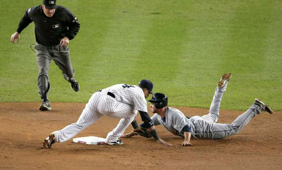Detroit Tigers' Omar Infante dives back into second as New York Yankees' Robinson Cano reaches to tag him in the eighth inning of Game 2 of the American League championship series Sunday, Oct. 14, 2012, in New York. Infante was called safe on the play by umpire Jeff Nelson. Photo: Charlie Riedel, AP / AP