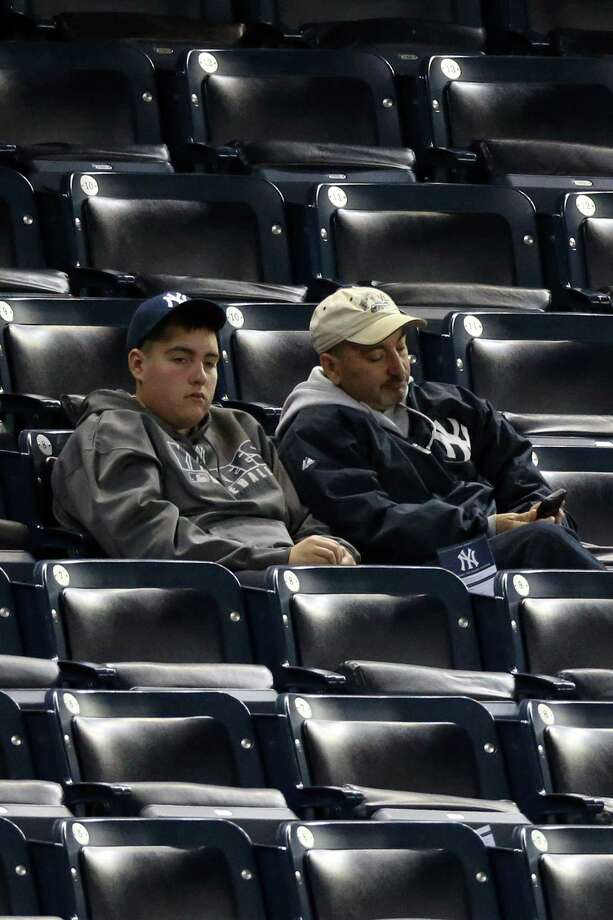 NEW YORK, NY - OCTOBER 14:  Two fans of the New York Yankees look on dejected after the Yankees lost 3-0 against the Detroit Tigers during Game Two of the American League Championship Series at Yankee Stadium on October 14, 2012 in the Bronx borough of New York City. Photo: Bruce Bennett, Getty Images / 2012 Getty Images