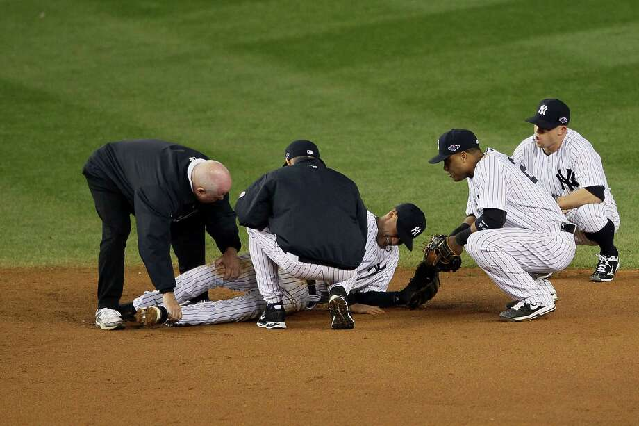 NEW YORK, NY - OCTOBER 13:  Derek Jeter #2 of the New York Yankees is tended to by trainer Steve Donohue (L), manager Joe Girardi (C), Robinson Cano #24 and Brett Gardner #11 (R) of the New York Yankees after Jeter hurt his leg in the top of the 12th inning against the Detroit Tigers during Game One of the American League Championship Series at Yankee Stadium on October 13, 2012 in the Bronx borough of New York City, New York. Photo: Alex Trautwig, Getty Images / 2012 Getty Images