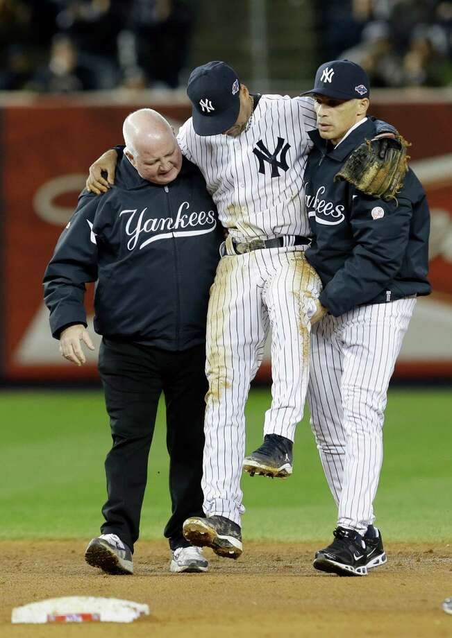 Trainer Steve Donohue, left, and New York Yankees manager Joe Girardi, right, help Yankees' Derek Jeter off the field after he injured himself during Game 1 of the American League championship series against the Detroit Tigers Sunday, Oct. 14, 2012, in New York. Photo: Paul Sancya, AP / AP