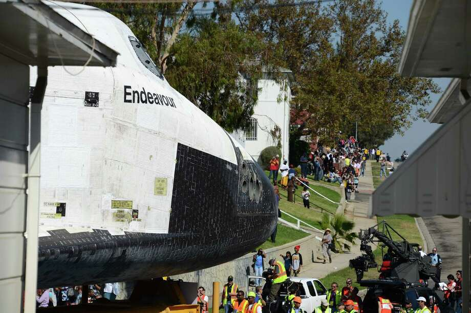 TOPSHOTS The Space Shuttle Endeavour inches its way through Crenshaw Drive, the narrowest part of its journey, as it is transported through the streets of Los Angeles on its final journey to its permanent museum home on October 13, 2012 in Los Angeles. The 170,000-pound (77,272 kg) shuttle will travel at no more than 2 mph (3.2 km per hour) along a 12-mile (19km) route from Los angeles International Airport (LAX) to its final home at the California Science Center. NASA's space shuttle program ended in 2011 after 30 years and 135 missions.    TOPSHOTS/ AFP PHOTO / Robyn BeckROBYN BECK/AFP/GettyImages Photo: ROBYN BECK, AFP/Getty Images / AFP ImageForum