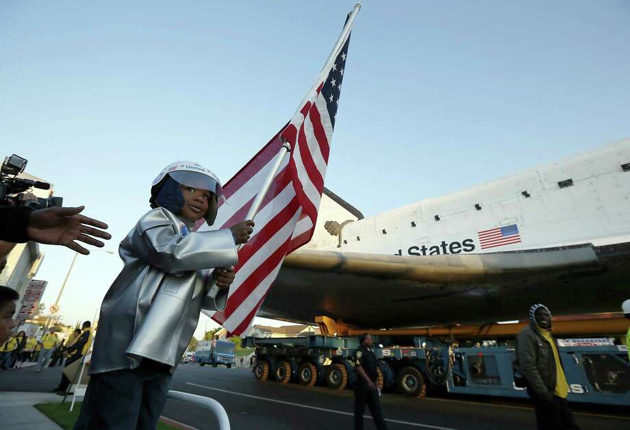 TOPSHOTS Amir Morris, 3, watches the Space Shuttle Endeavour being moved to the California Science Center in Los Angeles October 13, 2012. The 170,000-pound (77,272 kg) shuttle will travel at no more than 2 mph (3.2 km per hour) along a 12-mile (19km) route from LAX to it's final home at the California Science Center. NASA Space Shuttle Program ended in 2011 after 30 years and 135 missions.      AFP PHOTO/Lucy Nicholson/POOLLUCY NICHOLSON/AFP/GettyImages Photo: LUCY NICHOLSON, AFP/Getty Images / AFP