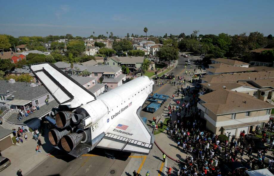 The Space Shuttle Endeavour slowly moves along city streets on a 160-wheeled carrier in Inglewood, Calif., Saturday, Oct. 13, 2012. After slowly surmounting a key obstacle, the shuttle Endeavour maintained a heading Saturday through the streets of Los Angeles toward its retirement home at a museum. Photo: Jae C. Hong, AP / AP