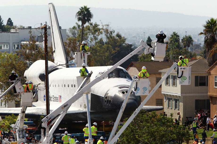Spectators take photographs as the space shuttle Endeavour makes its way through city streets in Inglewood, Calif., Saturday, Oct. 13, 2012. Endeavour's 12-mile road trip kicked off shortly before midnight Thursday as it moved from its Los Angeles International Airport hangar en route to the California Science Center. Photo: Patrick T. Fallon, AP / FR160581 AP