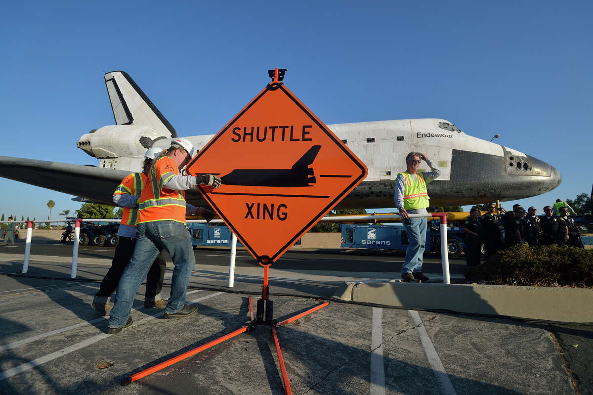 INGLEWOOD, CA - OCTOBER 13: Work crews set up a sign as the Space Shuttle Endeavour arrives at the Forum enroute to the California Science Center on October 13, 2012 in Inglewood, California. Endeavour is on its last mission - a 12-mile creep through city streets, past an eclectic mix of strip malls, mom-and-pop shops, tidy lawns and faded apartment buildings. Its final destination is the California Science Center in South Los Angeles where it will be put on display. NASA's Space Shuttle Program ended in 2011 after 30 years and 135 missions. (Photo by Jeff Gritchen-Pool/Getty Images) *** BESTPIX ***