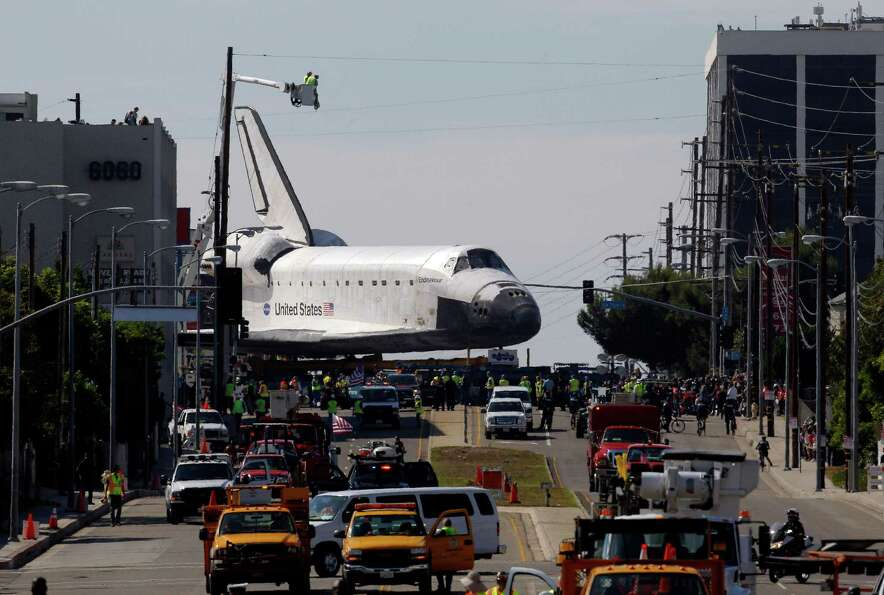 The Space Shuttle Endeavour slowly moves along city streets on a 160-wheeled carrier in Los Angeles,