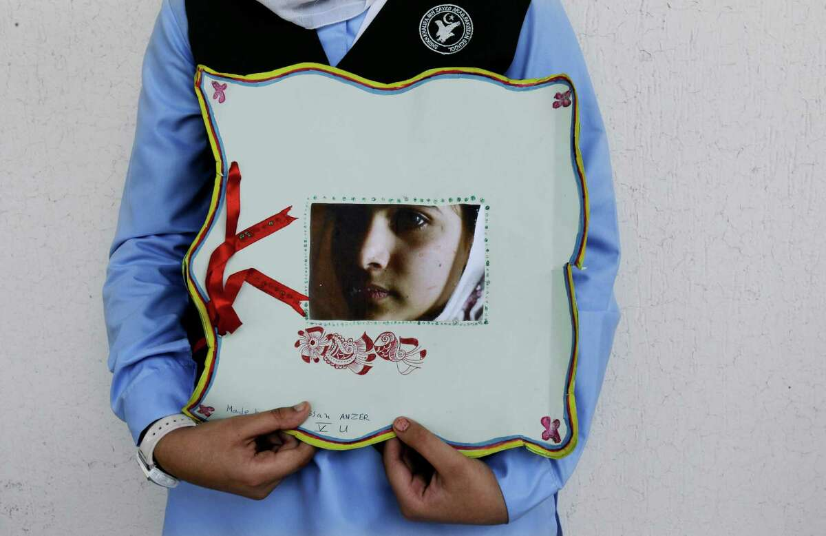 A Pakistani student holds a picture of 14-year-old schoolgirl Malala Yousufzai, who was shot last Tuesday by the Taliban for speaking out in support of education for women, during a tribute at the Pakistani Embassy in Abu Dhabi, United Arab Emirates. Pakistan airlifted a 14-year-old activist who was shot and seriously wounded by the Taliban to the United Kingdom for treatment Monday, a move that will give her access to the specialized medical care she needs to recover and also protect her from follow-up attacks threatened by the militants.
