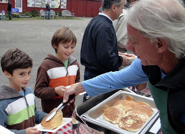 Peter Wormser, a Wakeman Town Farm volunteer, serves pancakes to William and Henry Matar, ages 9 and 7, of Westport, at the farm's annual pancake breakfast Sunday. Photo: Mike Lauterborn / Westport News contributed