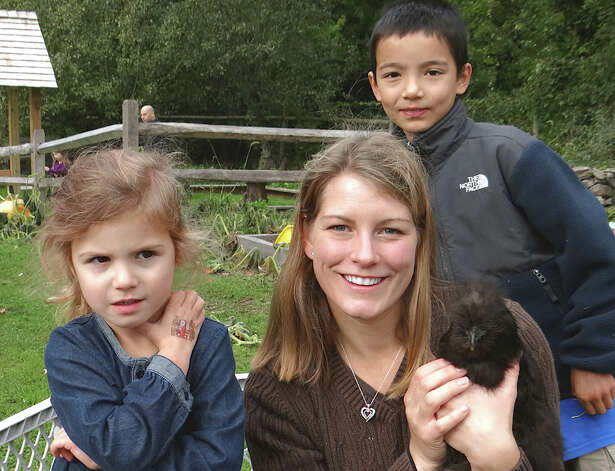 Wakeman Town Farm's Carrie Aitkenhead, center, with her chicken Nugget at Sunday's pancake breakfast was joined by Maggie Hertzmark, 4, of Riverside, and Matthew Fleming, 8, of Westport. Photo: Mike Lauterborn / Westport News contributed
