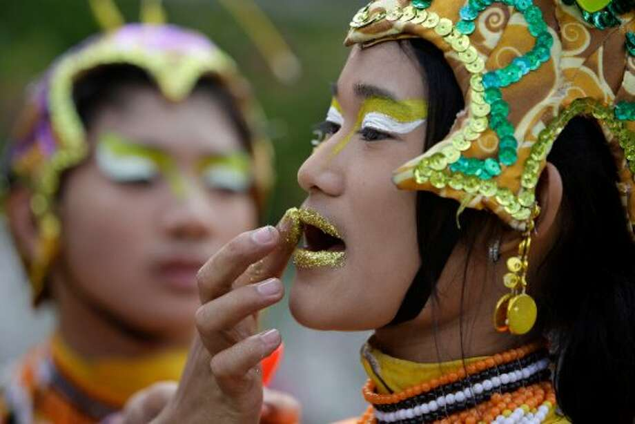"A Filipino student puts the finishing touches of their costume while they wait to perform during the annual ""Caracol"" festival at the financial district of Makati, south of Manila, Philippines, Sunday, Feb. 27, 2011. The event aims to promote public awareness on environmental issues and cultural heritage. (AP Photo/Aaron Favila) (AP)"