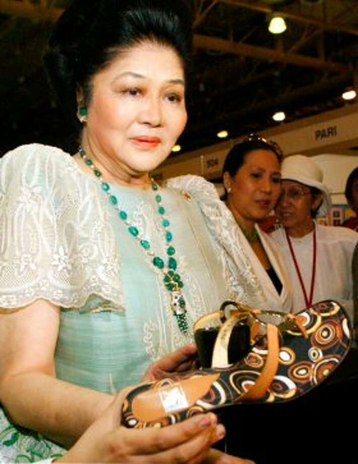 Flamboyant former Philippine First Lady Imelda Marcos reacts as she is offered a pair of shoes by an exhibitor at the opening of the exhibit of Philippine entertainment products at a Manila convention center Friday June 18, 2004. Marcos, one of Asia's most beautiful women and was famous for her collection of thousands of pairs of shoes during her husband's regime, is to appear later before a city court as she files a suit to stop the screening of a documentary about her, saying she'd only consented to an interview for the film because she thought it was a school project and  not a commercial movie. (AP Photo/Bullit Marquez) (AP)