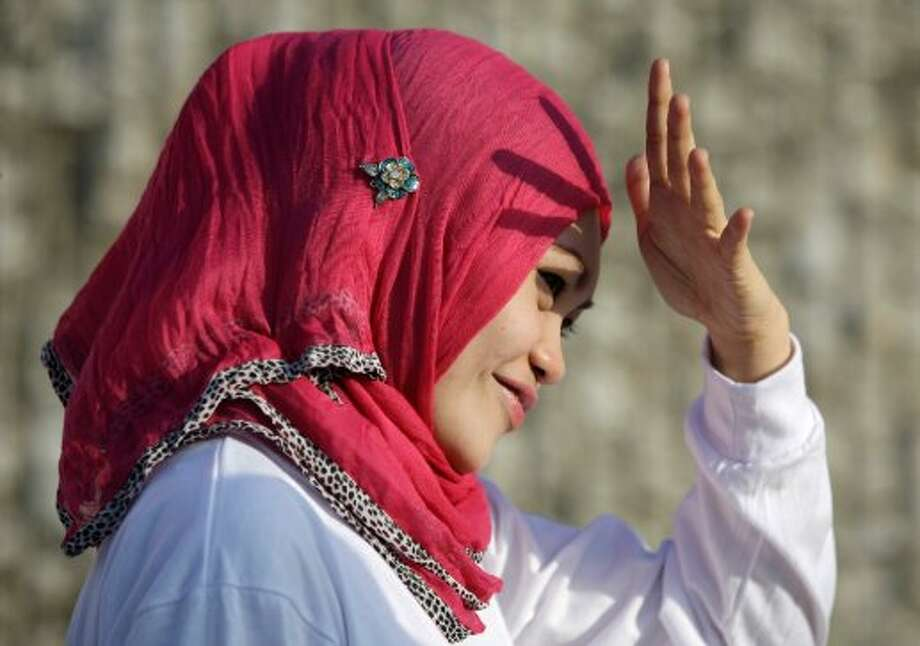 A Filipino Muslim shields her face from the sun before the start of a fun run in support of a preliminary peace agreement between the government and the nation's largest Muslim rebel group in suburban Quezon city, north of Manila, Philippines on Sunday, Oct. 14, 2012. Philippine officials hope a preliminary peace deal the government recently clinched with the Moro Islamic Liberation Front will eventually turn the 11,000-strong insurgent group into a formidable force against the remnants of the Abu Sayyaf and other radicals, including several Indonesian and Malaysian militants believed to be taking cover in the southern Mindanao region.(AP Photo/Aaron Favila) (AP)