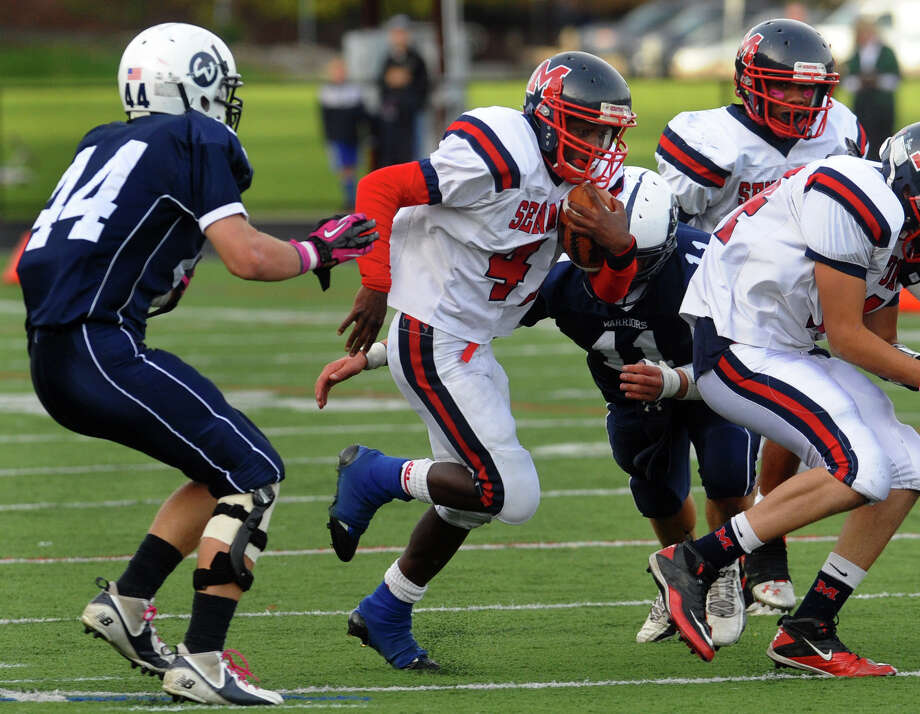 McMahon's #41 Kentrell Snider weaves his way through with the ball as Wilton defenders converge, during boys football action in Wilton, Conn. on Friday October 13, 2012. Photo: Christian Abraham / Connecticut Post