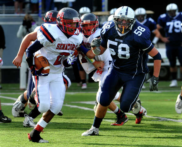 McMahon's #2 Malik Whittaker gains yardage as Wilton's #58 Mike Lasala tracks him, during boys football action in Wilton, Conn. on Friday October 13, 2012. Photo: Christian Abraham / Connecticut Post