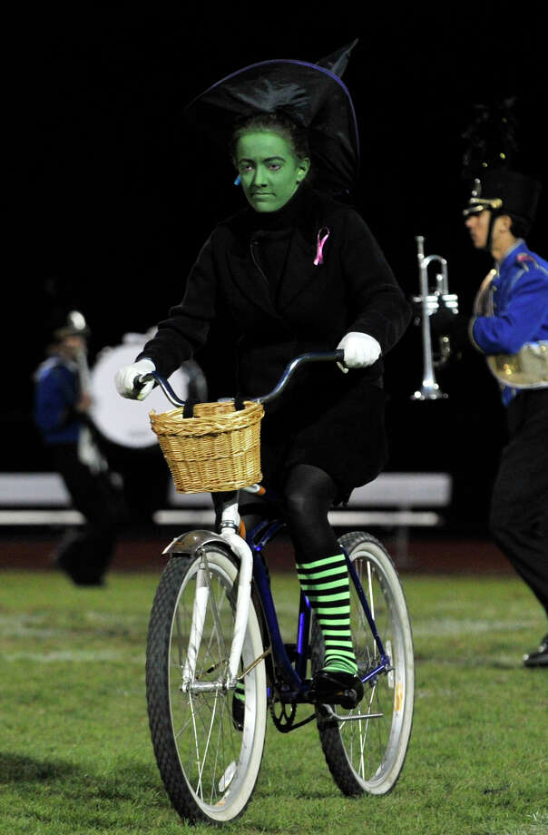 Brookfield High School drum major Victoria Dahm rides a bike dressed as the Wicked Witch of the West as the rest of the marching band and color guard perform at the annual Quest for the Best marching band and color guard competition at Bethel High School on Saturday, Oct. 13, 2012. Photo: Jason Rearick / The News-Times
