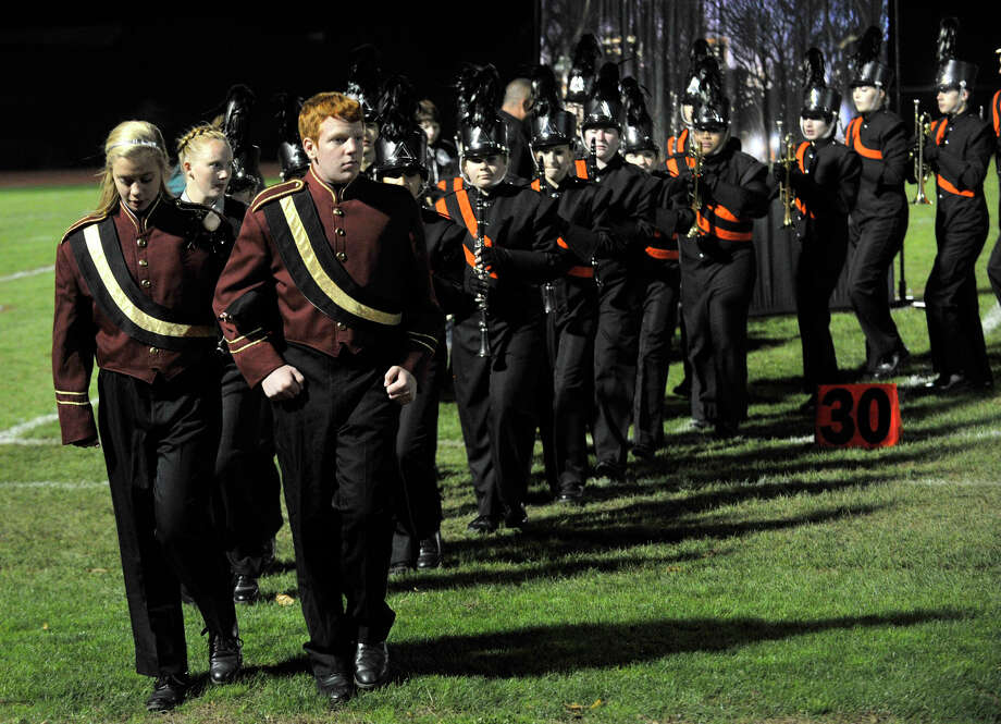 Jordan Smith, left, and Hunter Sprock escort the Shelton High School marching band and color guard off the field after performing at the annual Quest for the Best marching band and color guard competition at Bethel High School on Saturday, Oct. 13, 2012. Photo: Jason Rearick / The News-Times