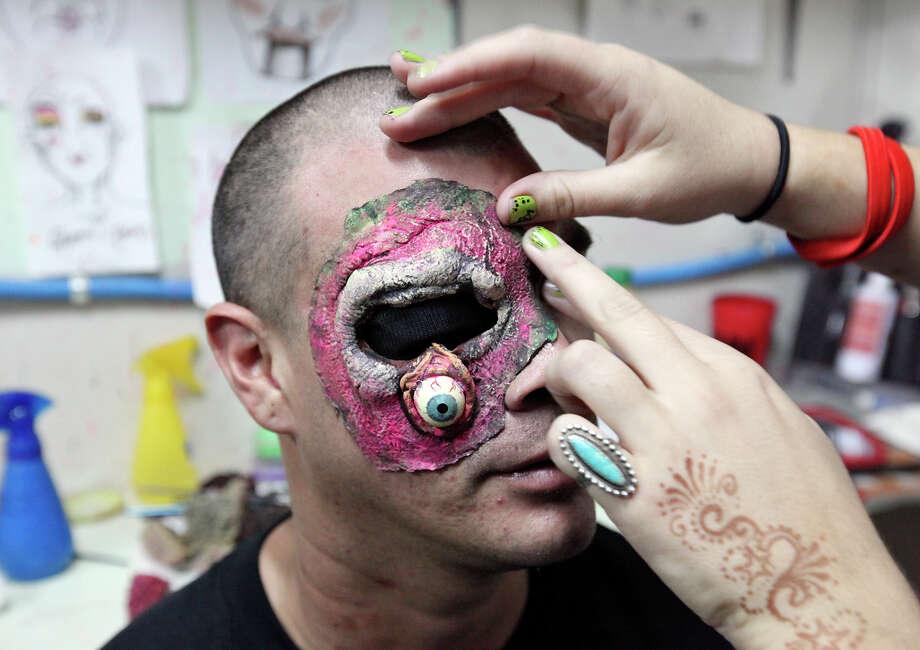 Makeup artist Shauna Burns, 23, applies a fake eye to actor David Hernandez, 29, Sunday Oct. 14, 2012 at Nightmare on Grayson. Photo: Edward A. Ornelas, San Antonio Express-News / © 2012 San Antonio Express-News