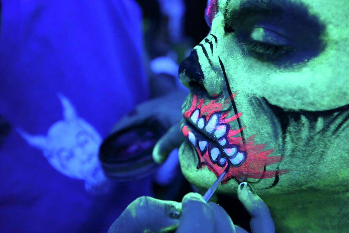 Makeup artist Burns applies zombie makeup to under black-light.