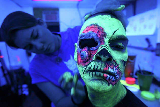 Makeup artist Shauna Burns, 23, applies zombie makeup to actor David Hernandez, 29, under black-light Sunday Oct. 14, 2012 at Nightmare on Grayson. Photo: Edward A. Ornelas, San Antonio Express-News / © 2012 San Antonio Express-News