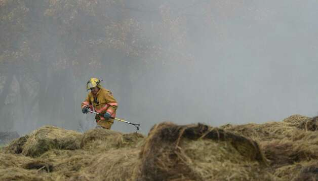 A firefighter  from Rensselaer County sifts through the hay looking for hot spots at the scene of a barn and hay fire at 38 Hemstreet Road in Schagticoke, N.Y. Oct. 15, 2012. (Skip Dickstein/Times Union) Photo: SKIP DICKSTEIN