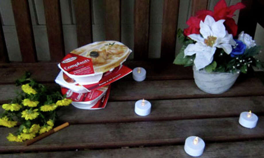A touching memorial to the late Paul Rake is tucked ina corner just outside St. John's Episcopal Church in New Milford. Left in memory of Mr. Rake are candles, flowers, a few coins and several frozen dinners. Photo: Norm Cummings