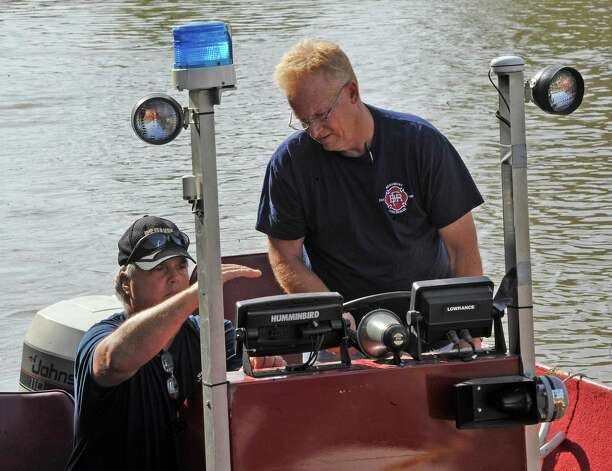 Beaumont firemen with Search and Rescue, Mark Phillips, left, and Capt. Mike Hall right, use a sonar equipped boat to search the LNVA canal near the bridge Monday morning for the missing driver. Monday afternoon, police and firemen found a body, in the canal near Major Drive, that could be that of a Warren man who went missing late Friday night after his truck plunged into the LNVA canal near the Eastex Freeway service road turn-around.  Dave Ryan/The Enterprise