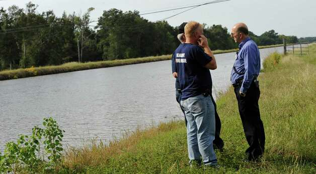 Beaumont firemen with Search and Rescue, Mark Phillips, left, and Capt. Mike Hall middle, meet with Beaumont Fire Department Capt. Brad Penisson, right, after searching the LNVA canal near the bridge Monday morning for the missing driver. Monday afternoon, police and firemen found a body, in the canal near Major Drive, that could be that of a Warren man who went missing late Friday night after his truck plunged into the LNVA canal near the Eastex Freeway service road turn-around.  Dave Ryan/The Enterprise