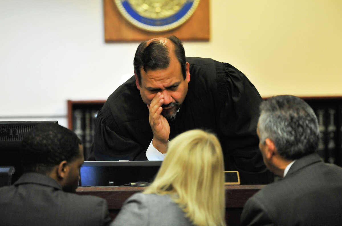 Judge Ron Rangel of the 379 District Court speaks to defense attorneys David Henderson (left) Jan Ishy (center) and defense attorney Joel Perez as the sentencing phase of convicted capital murderer James Morrison's trial begins Monday, Oct. 15, 2012.