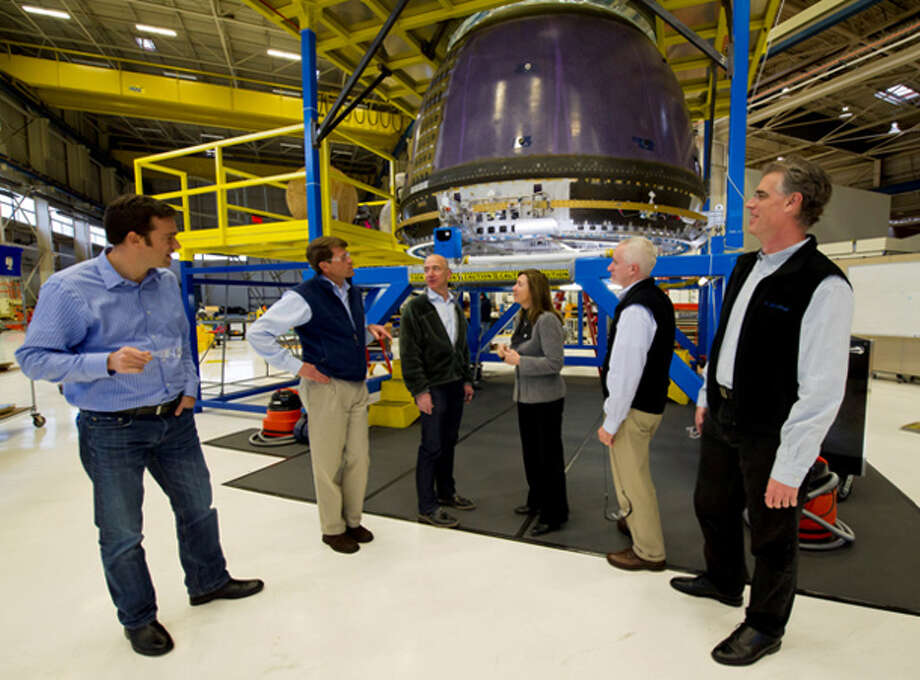 Meanwhile, Bezos' company Blue Origin is developing craft to carry people and supplies into orbit. Here, Bezos, third from left, shows Blue Origin's crew capsule to NASA Deputy Administrator Lori Garver, fourth from left, as Blue Origin employees look on at the company's headquarters in Kent, Wash., on Dec. 8, 2011. Photo: NASA/Bill Ingalls