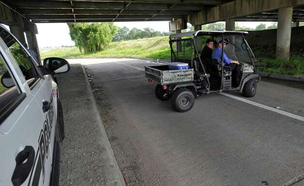 Capt. Brad Penisson, right, and Police Officer Don Bracker, take an ATV to go search the banks along the canal before lunch time. Later Monday afternoon, police and firemen found a body, in the canal near Major Drive, that could be that of the Warren man who went missing late Friday night after his truck plunged into the LNVA canal near the Eastex Freeway service road turn-around.  Dave Ryan/The Enterprise