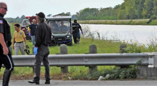 Police and fire officials gather around the ATV on the canal bank, just past Major Drive, as the vehicle carries out the body.  Officials were not saying if it was Stephen Dvorman, the Warren man who went missing late Friday night after his truck plunged into the LNVA canal near the Eastex Freeway service road turn-around.  Dave Ryan/The Enterprise