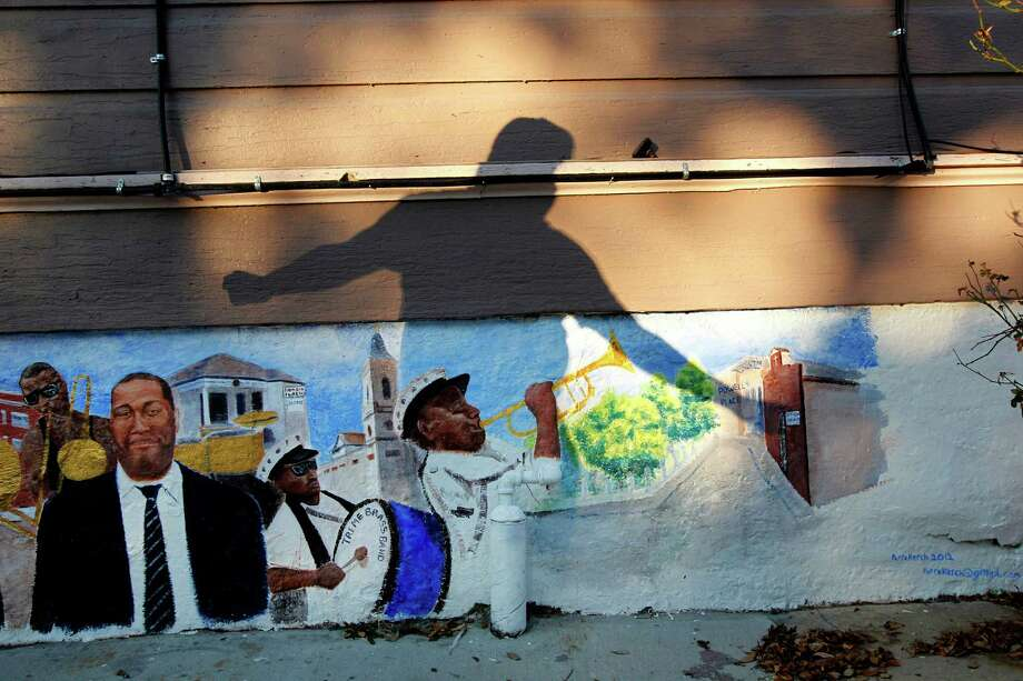 The shadow of Shannon Powell, lifelong resident and musician, is seen falling on a mural in front of his house in the Treme section of New Orleans. The historic New Orleans neighborhood where immigrants, free people of color and slaves were allowed to own property, worship on Sundays and gather in public to dance and play music, has hit a milestone. It was roughly 200 years ago that cottages were built and a community established just beyond the French Quarter in the area named for French milliner and property owner, Claude Treme. The neighborhood is considered one of America's most unique. Photo: Gerald Herbert, Associated Press / AP