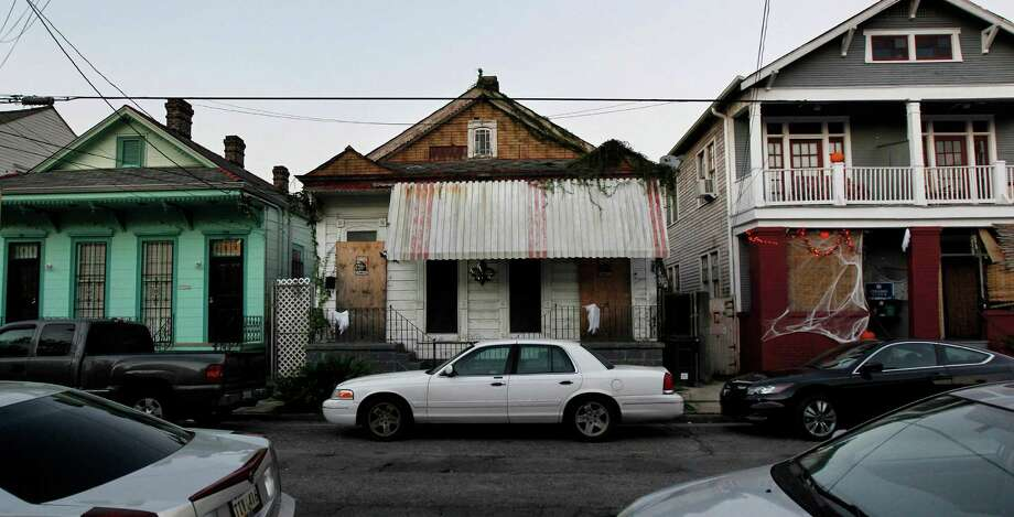 "In this Oct. 11, 2012 photo, a blighted home sits between two residences in the Treme section of New Orleans. The historic New Orleans neighborhood where immigrants, free people of color and slaves were allowed to own property, worship on Sundays and gather in public to dance and play music, has hit a milestone. It was roughly 200 years ago that cottages were built and a community established just beyond the French Quarter in the area named for French milliner and property owner, Claude Treme. The neighborhood is considered one of America's most unique, and it is getting a new lease on life thanks, in part, to the spotlight provided by HBO's series, ""Treme."" It's also at the center of a $4 billion redevelopment plan. (AP Photo/Gerald Herbert) Photo: Gerald Herbert, Associated Press / AP"